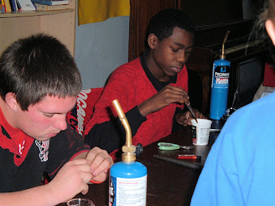 James Ray and Patrick Howard, two neighborhood youth, making pendants during a silversmith class taught by Jerry Day at the Goodlife Center.