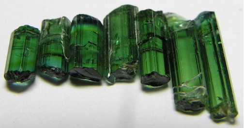 seven green tourmaline crystals in a row.jpg