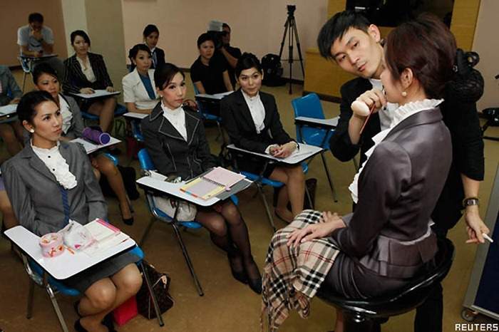 Transsexual flight attendants (from L to R, sitting): Phuntakarn Sringern, 24, Chayathisa Nakmai, 24, and Nathatai Sukkaset, 26, look at an instructor during a make-up training session at PC Air office in Bangkok February 9, 2011. A newly formed Thai airline PC Air wants to make a different from their competitors by hiring the transsexual flight attendants. Be pretty and be feminine are the qualification the ladyboys should have to join a new charter airline that will begin the operation in early April. The airline has recruited four ladyboys, 19 female and seven male but said they will need to employ more of transsexual on their flights in the future.  REUTERS/CHaiwat Subprasom (THAILAND - Tags: SOCIETY ODDLY TRANSPORT)
