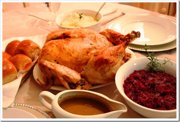 Boneless turkey roast served with a bowl of gravy, basket full of dinner rolls and cranberries