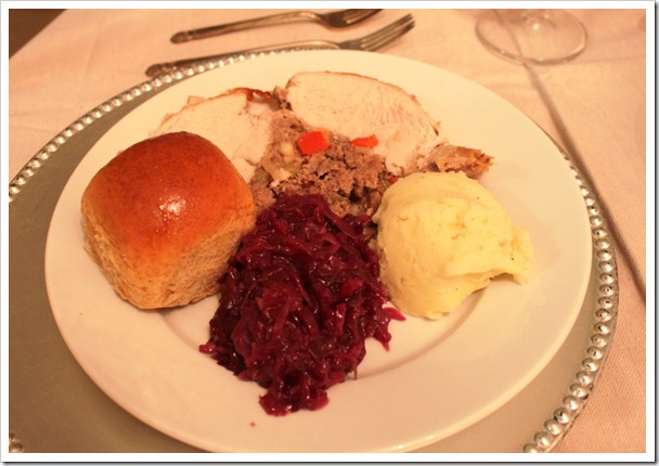 slice of roasted turkey with mashed potatoes, cranberries, stuffing and a bread roll.