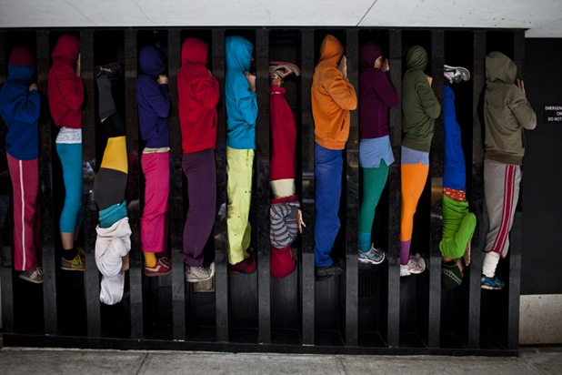 "Performers situate themselves into position during a piece entitled ""Bodies in Urban Spaces"" by choreographer Willi Dorner.  Starting at sunrise, the performers inched their way into different spaces throughout lower Manhattan.