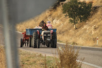 Turkish farmer, his wife and daughter on a tractor on their way to the fields for harvesting