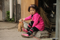 Little Chinese girl petting her cat in her front porch, Shanghai, China