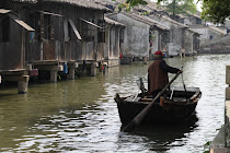 Old man with his boat in the canals of Wuzhen