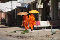 Two monks begging for streets at people's doors in the streets of Kampot