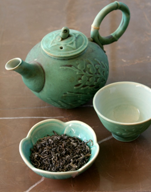 green tea with teapot and tea leaves