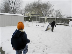 Boys running to play in the snow in the backyard.