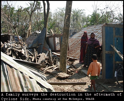 Bangladeshi women survey the destruction of Cyclone Sidr