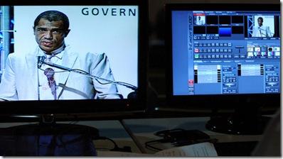 foto de um homem operando uma mesa de áudio e vídeo