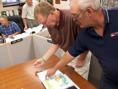 Washington County Supervisors Jim Davis (right) and Jim Rosien look over a new flood plane map at the 9/15/09 meeting (KCII NEWS)