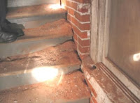 The bricks in the stairwell are soft and falling apart.  The red dust on the stairs is the deteriorated brick from the wall.<br />