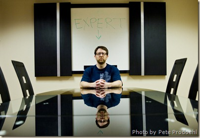 """Man sitting at the head of a table with """"EXPERT"""" written on a whiteboard behind him"""