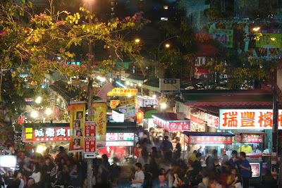 The crowd, and the densely arranged stalls in the market.