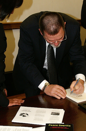 Photo of Ben Hoffman Signing Peace Guerilla Book at the Peace Professionals Event