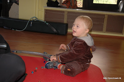 Radosna zabawa z kulkami - jedna ręka trzyma rurę, druga wkłada kulki.