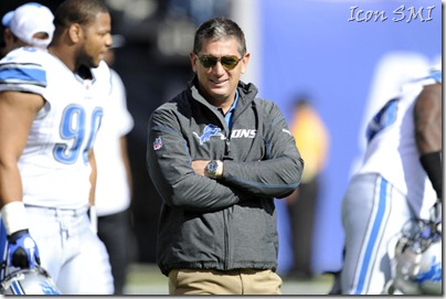 Detroit Lions head coach Jim Schwartz grins as Ndamukong Suh walks past him.