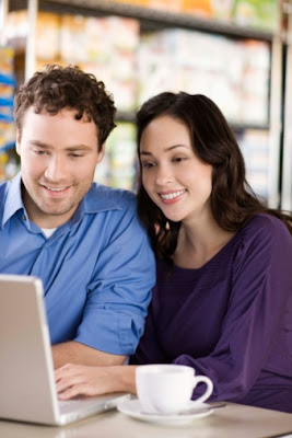 A smiling couple using a computer.