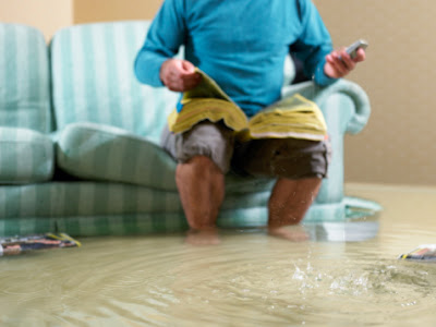 Man sitting in a flooded living room looking for faxless payday loans.