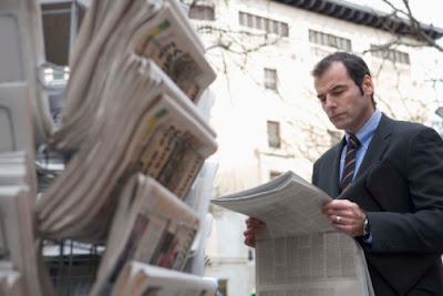 A businessman reading a local newspaper.