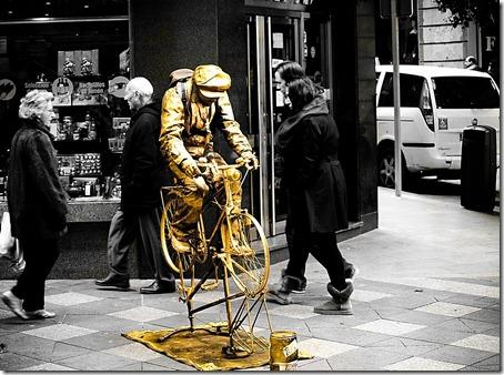 El ciclista dorado espera unas monedas para pedalear.
