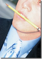 business man biting pencil