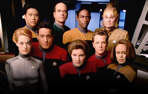 em cima: Kim, o médico, Tuvoc, Neelix; em baixo: Sete, Chakotay, Janeway, Paris, Torres