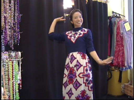 Whos crazier - the lady or the dress? Grace wears a psychedelic 1970s mock-neck dress.