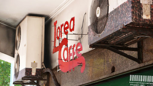 Lorea Caffé Logo in Oblique Perspective Totally Squeezed between Two Air Conditioners in Buenos Aires, Argentina