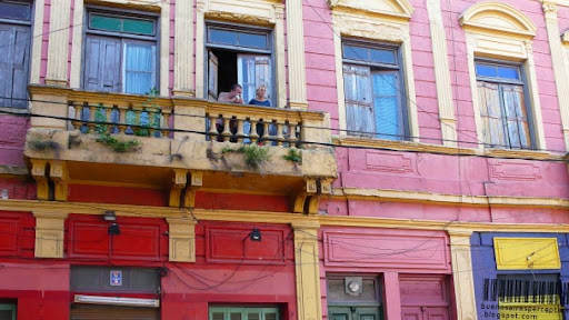 Porteños on old ramshackle balcony with a green feature of a colorful house in La Boca, Buenos Aires