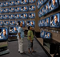 Father and son watch Obama at TV store