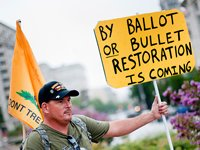 Bagger with sign reading 'By ballot or bullet, restoration is coming'