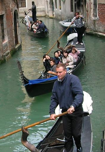 Japoneses passeando em gôndolas por canais de Veneza