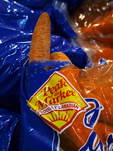 a carrot is poking out of a hole in a bag labelled 'peak of the market'