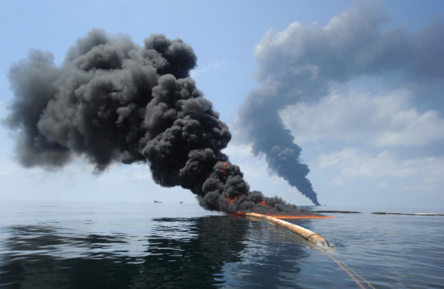 "Dark clouds of smoke and fire emerge as oil burns during a controlled fire in the Gulf of Mexico, May 6, 2010. The U.S. Coast Guard working in partnership with BP PLC, local residents, and other federal agencies conducted the ""in situ burn"" to aid in preventing the spread of oil. (REUTERS / Mass Communication Specialist 2nd Class Justin Stumberg-US Navy)"