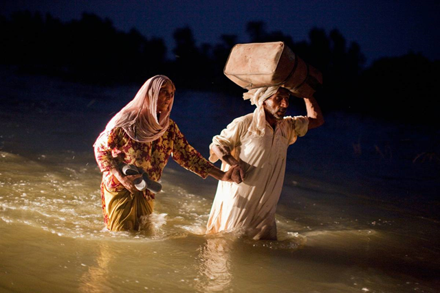 A man and a woman displaced by floods, walk through flood waters on Sunday in the village of Baseera near Muzaffargarh in Punjab, Pakistan. Daniel Berehulak / Getty Images