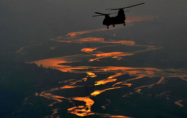 A US rescue helicopter carrying Pakistani flood affected victims flies above Kallam, a town of Swat Valley, on September 2, 2010. A. MAJEED / AFP / Getty Images