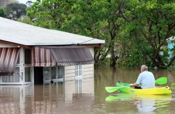 A resident evacuates his flooded home by kayak in Bundaberg on December 29, 2010 after entire towns were inundated by the worst deluges in decades. Thousands of people prepared to flee floods in Australia's north-east Thursday as rising waters swamped towns, roads and railways in an 'unprecedented' multi-billion-dollar disaster. AFP / Pool / Jono Searle