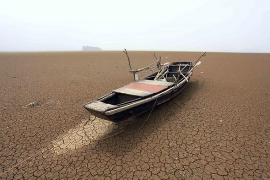 A fishing boat is stranded on the cracked bed of Poyang Lake in Jiujiang, East China's Jiangxi province, 4 May 2011. Poyang Lake is at its lowest level in more than 50 years. The lake is drying up because of less rainfall this year and an historic drought. Xinhua Photo / Zhang Jun