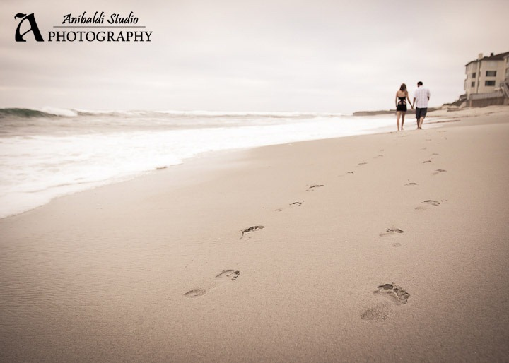 beach footprints engaged couple