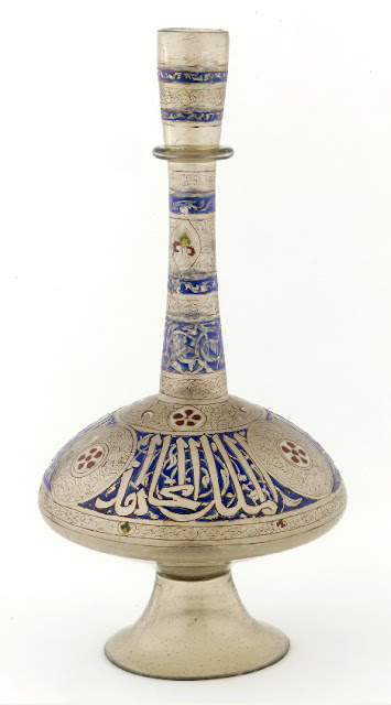 "Inscribed along the widest part of this bottle in thuluth script is the Arabic phrase, ""Glory to our master, the sultan, al-Malik, al-Mujahid, the wise, the just."" Syria. Mid-14th century. 47.9 x 24.8 cm. Thuluth script. Courtesy of the Freer Gallery of Art, Smithsonian Institution."