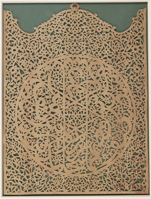This dcoupage panel in the shape of a closed altar piece includes a central roundel decorated with interlacing letters whose stems form a central six-pointed star. The round inscription is difficult to decipher, and may comprise a wise saying or a verse from the Koran. In the middle of the upper arch, a round hook suggests that it was used as a wall hanging.