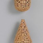 These beads feature superb patterns of scrolling vines whose bifurcations elegantly extend the design to fit the required space. The patterns recall those of the beveled style of the ninth century, although these possess clearer lines, perhaps owing to the medium.