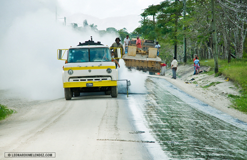 Spreading hot tar on Palmar Road, Orange Walk Town, Belize.