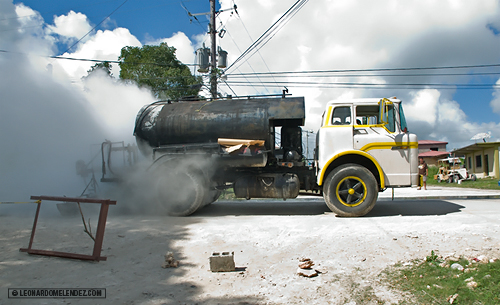 Steaming hot tar spread on street, Louisiana Area, Orange Walk Town, Belize.