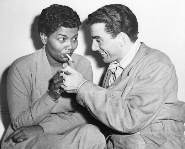 Louis Bellson lighting Pearl Bailey's cigarette, London, England, November 17, 1952.jpg