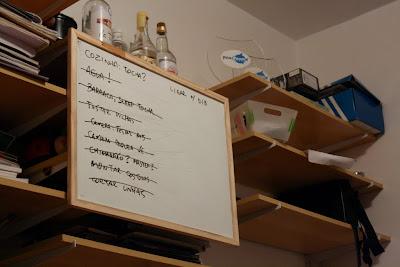 Lousa com notas pendurada na estante da sala