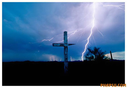 Cross Arizona This wooden, weathered cross was over 7 feet tall, and was photographed in the Tohono O'odham Nation.  The wide-angle lens view of an approaching storm is one of my favorites.  1991