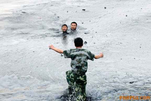 A worker attempts to rescue his co-worker from drowning in the oil slick while attempting to fix an underwater pump during the oil spill clean-up operations at Dalian's Port in Liaoning province July 20, 2010. A pipe transporting crude oil from a ship to a storage tank blew up on Friday evening, causing a second pipeline nearby to  explode also, according to Xinhua News Agency. No one was injured. The port has since resumed normal container operations. REUTERS/Jiang He/Greenpeace (CHINA - Tags: ENERGY ENVIRONMENT IMAGES OF THE DAY DISASTER) NO SALES. NO ARCHIVES. FOR EDITORIAL USE ONLY. NOT FOR SALE FOR MARKETING OR ADVERTISING CAMPAIGNS. MANDATORY CREDIT