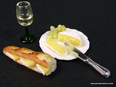 Miniature Baguette filled with ham and brie cheese accompanied by a plate of brie with grapes